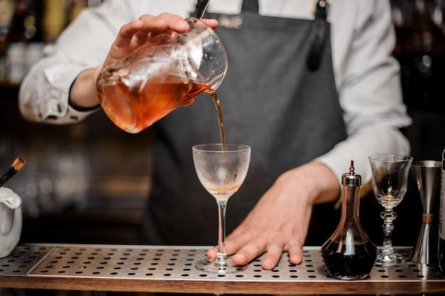 バーテンダーがカクテルグラスに新鮮なアルコール飲料を注ぐ