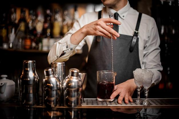 ガラスの新鮮な夏のアルコールカクテルをかき混ぜるバーテンダー