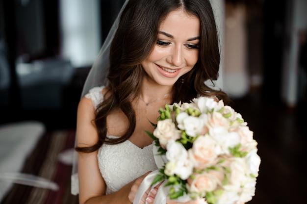花嫁の朝の準備。ウェディングブーケと白いベールの美しいと笑顔の花嫁