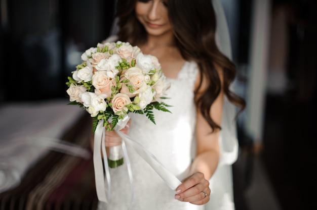 花嫁の朝の準備。白いドレスとベールのウェディングブーケに身を包んだ美しい花嫁