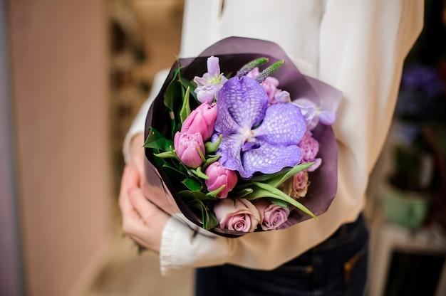 Женщина одета в белую блузку с букетом цветов в фиолетовой бумаге