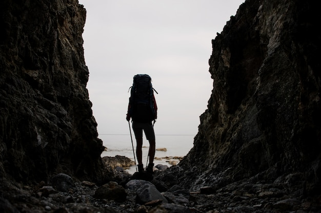 ハイキングのバックパックと海の海岸線の岩の間に立っているシルエットガール