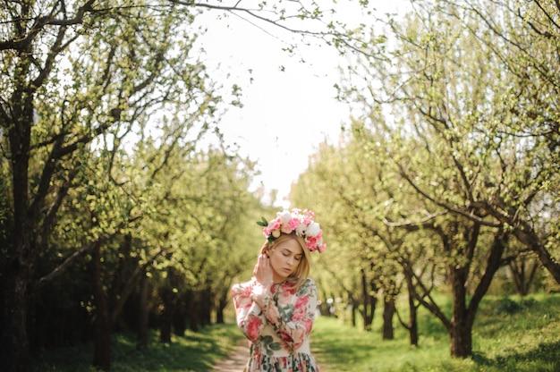 花のドレスとピンクの花輪に身を包んだ金髪美人の優しい肖像画