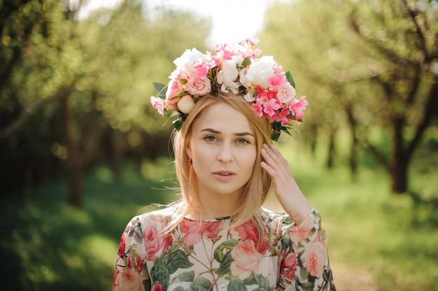 花のドレスとピンクの花輪に身を包んだ金髪美人