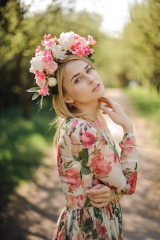 花のドレスとピンクの花輪に身を包んだ美しい金髪の女性の肖像画