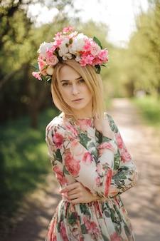 花のドレスとピンクの花輪に身を包んだ金髪美人の垂直の肖像