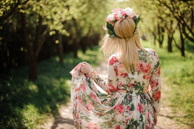 花のドレスと彼女の頭に花輪を着た金髪の女性の背面図