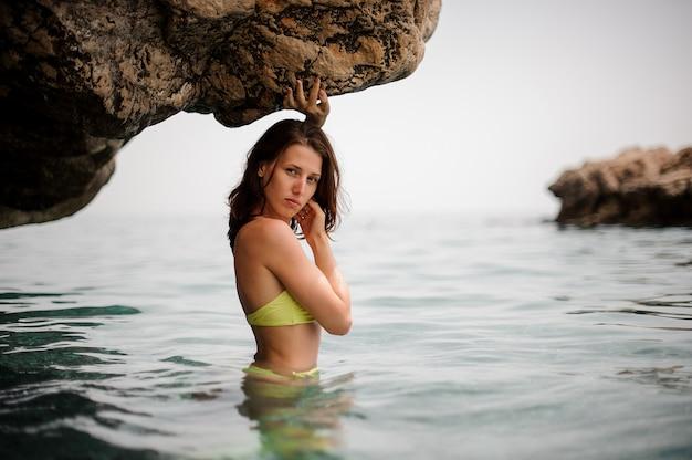 水の洞窟で黄色のビキニで美しい若い赤毛の女の子