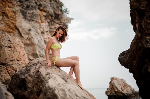 岩の上に座っている黄色のビキニで美しい少女