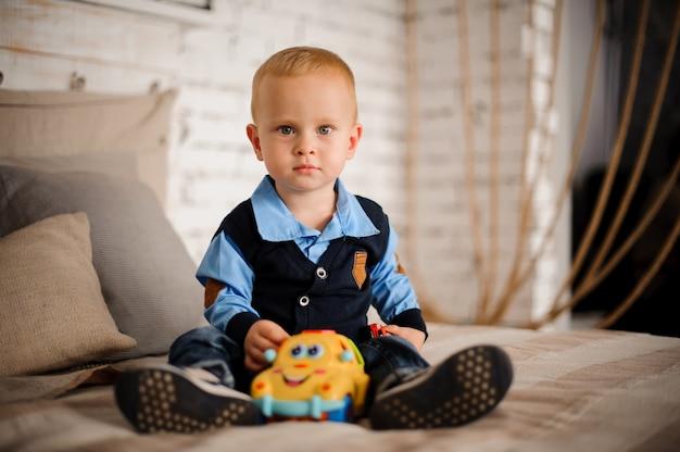 Милый маленький мальчик сидит на кровати с игрушкой в руках