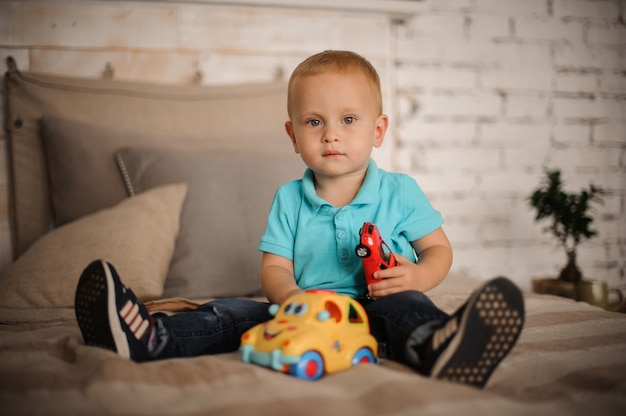 Милый маленький мальчик сидел на кровати с игрушкой автомобиля