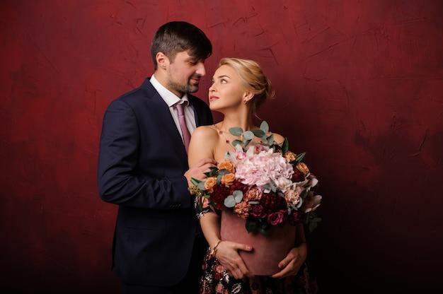 Молодой человек обнимает свою женщину с букетом цветов и смотрит ей в глаза