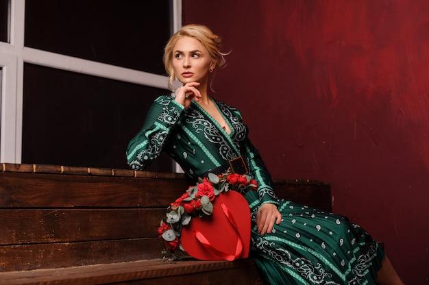 Женщина сидит на лестнице с красной коробкой роз