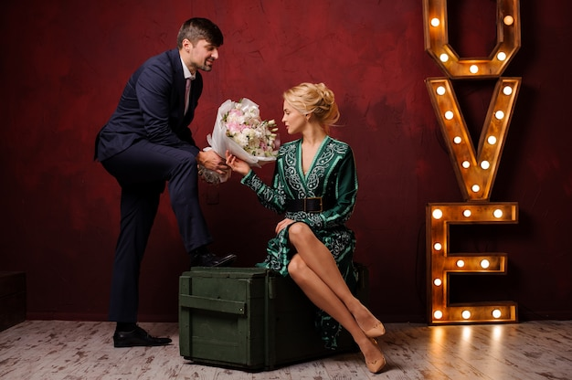 Женщина в зеленом платье сидит на коробке и получает букет своего мужчину