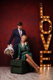 Женщина в зеленом платье сидит на коробке со своим мужчиной