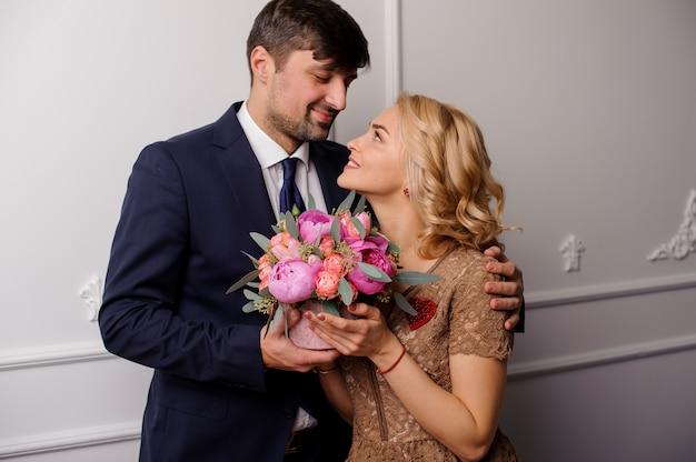 Молодой человек обнимает свою женщину с букетом цветов и смотрит в глаза