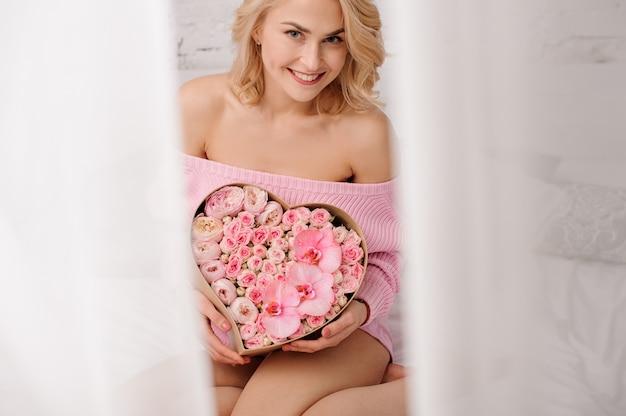 バラ色の牡丹、蘭の花、バラのハート形ボックスを保持しているベッドの上に座っているピンクのシャツと笑顔の女性