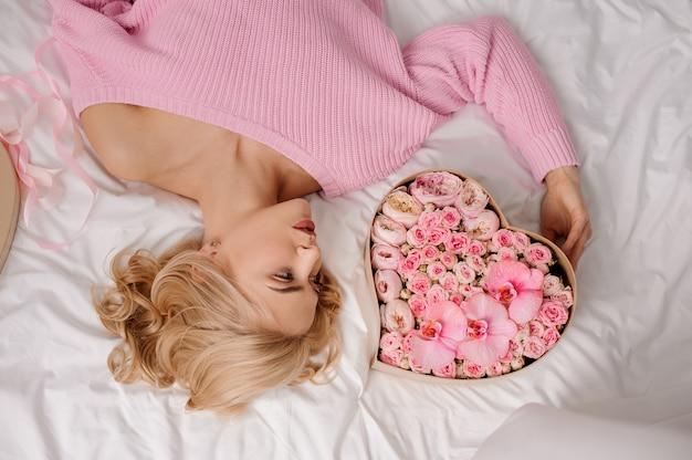 Женщина с розовой рубашкой лежала на кровати возле коробки в форме сердца из розовых цветов