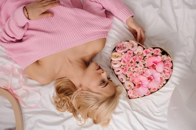 Женщина в розовой рубашке лежит на кровати и смотрит на коробку в форме сердца из розовых цветов