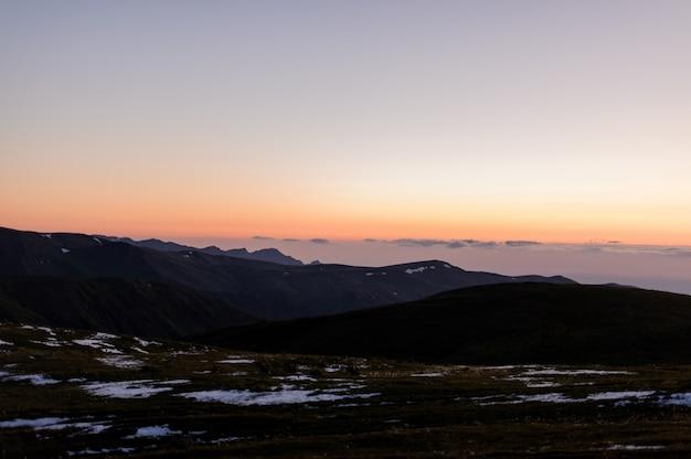 日没の曇り空を背景に草や雪の残骸で覆われた丘の風景