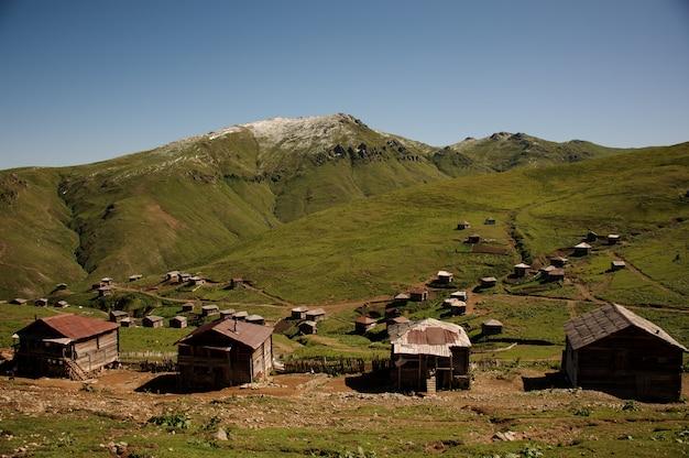 晴れた空を背景に緑の草と家で覆われた丘の風景
