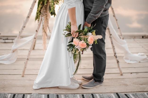 男と彼の花嫁が結婚式の上に立って