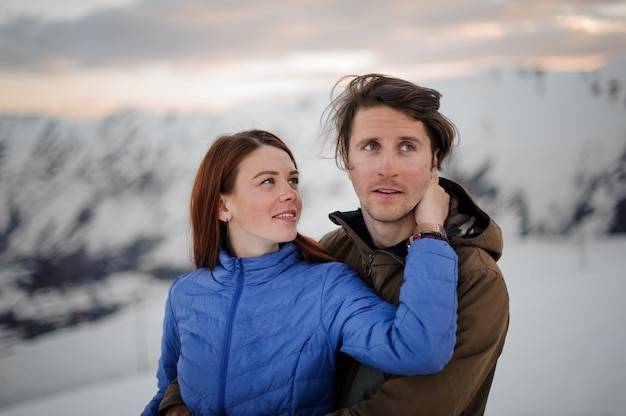 若いカップル、女の子とボーイフレンド、雪山の景色を眺める