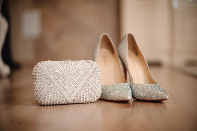 光沢のある小石の花嫁の靴は白いクラッチの横に立つ