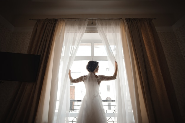 Красивая невеста в белом свадебном платье открывает шторы
