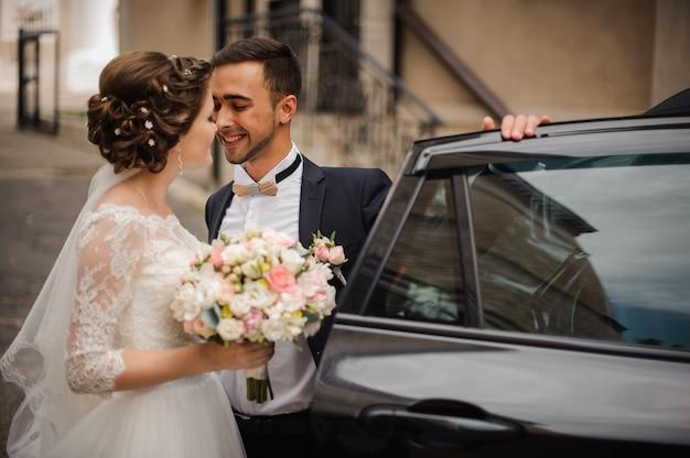 新郎は結婚式の車のドアを開け、花嫁にキスしようとする