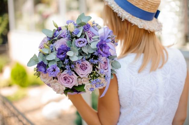 Женщина держит букет из роз, эвкалиптов, синих маков и суккулентов