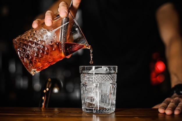 グラスに明るい赤いアルコールカクテルを注ぐバーテンダーのクローズアップ