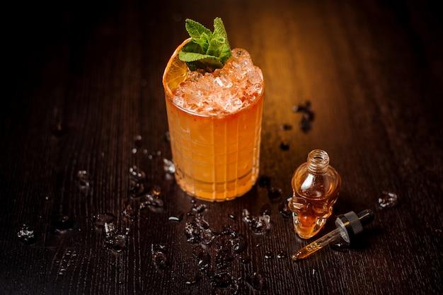 Маленькая бутылка в форме черепа и апельсиновый коктейль