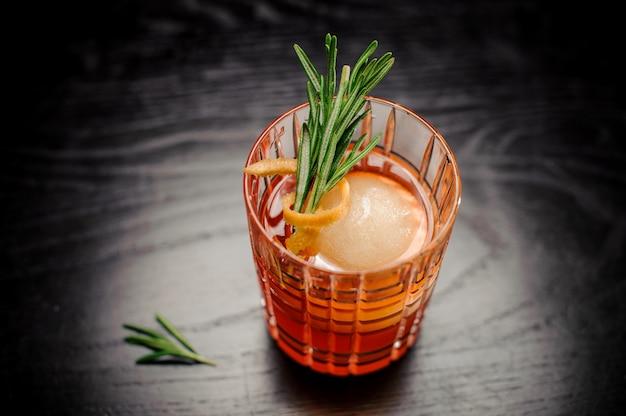 ローズマリー、オレンジの皮、アイスボールと赤いアルコールカクテル