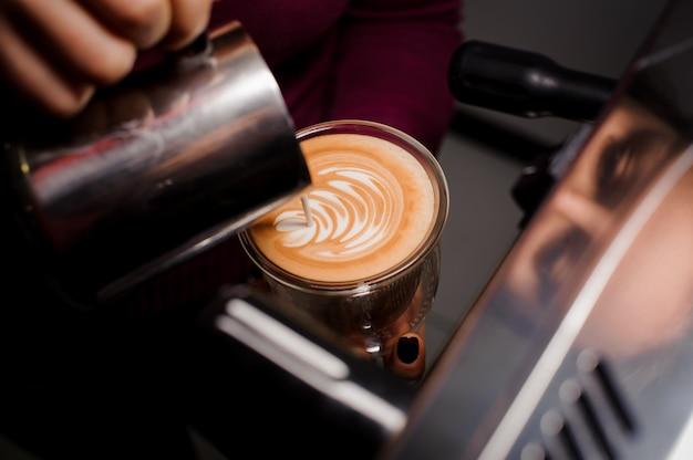高いガラスのカップで熱いラテコーヒー