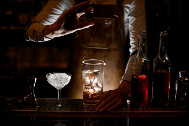Бармен наливает эссенцию из маленькой стеклянной бутылки