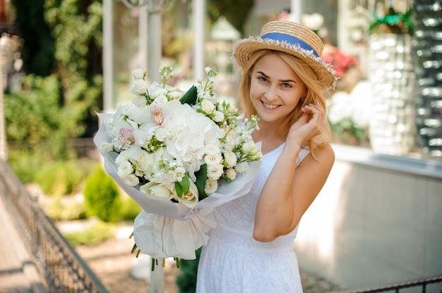 Белый свадебный букет в руках милой девушки в шляпе