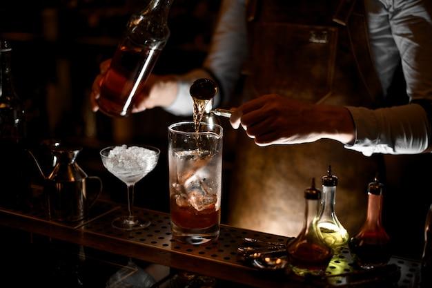 バーテンダーがスチールジガーから計量ガラスカップにアルコールを注ぐ