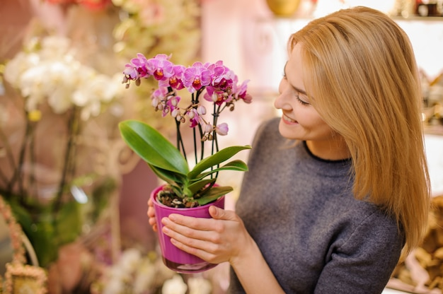 Девушка держит красивую розовую орхидею в горшке