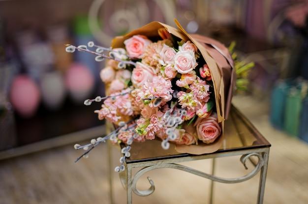 テーブルの上に横たわるネコヤナギで飾られたバラ色の花の素晴らしい花束