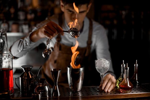 炎の中でスプーンからスチールシェーカーにエッセンスを注ぐ魅力的な男性バーテンダー