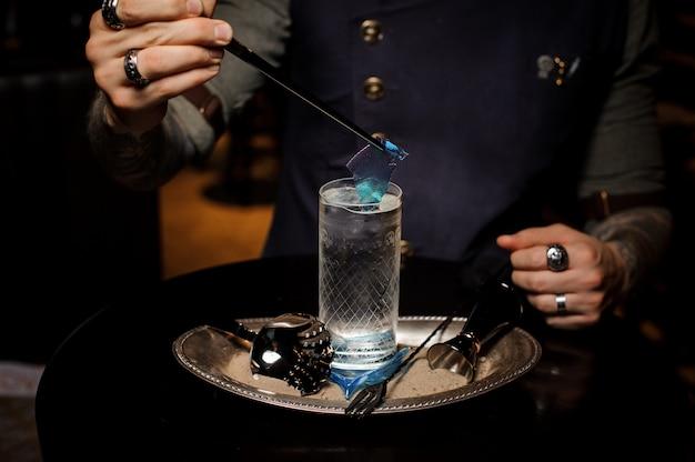 バーテンダーが透明な青いキャラメルシートでガラスを飾る