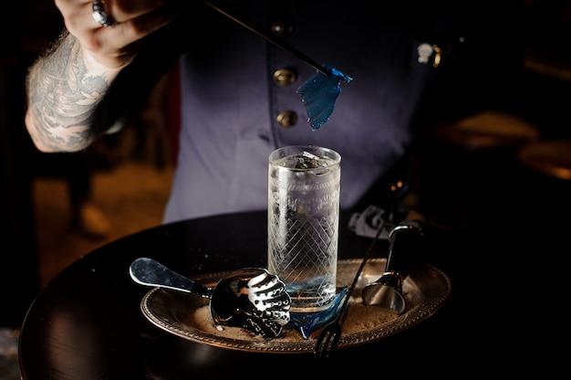 バーテンダーが透明な青いキャラメルシートでカクテルグラスを飾る