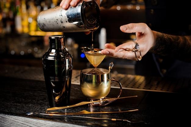 銅のカップにアルコールカクテルを注ぐ入れ墨のバーテンダー