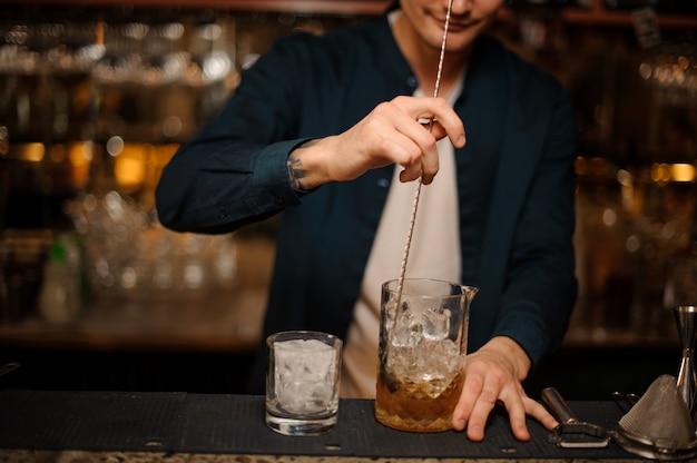 巻き毛のバーテンダーが昔ながらのアルコールカクテルを準備します