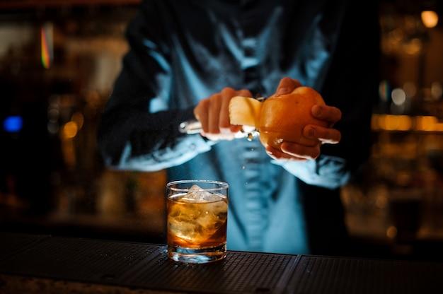 青いシャツを着たバーマンがアルコールカクテルの準備を終了します