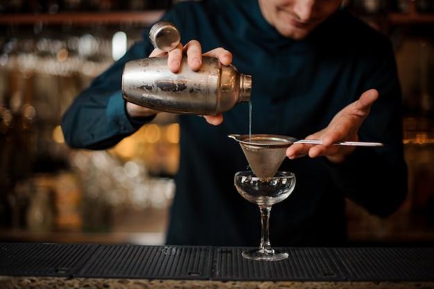 バーマンはアルコールカクテルをシェーカーからグラスに注いだ