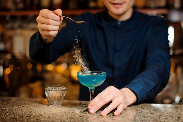 バーテンダーはブルーラグーンのアルコールカクテルの準備を終えています