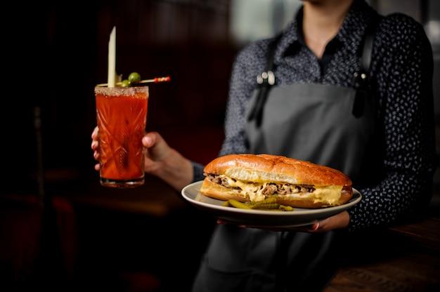 Девушка держит белую тарелку с вкусным мясным сэндвичем и красным коктейлем