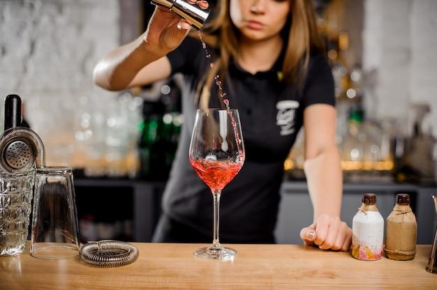 Барменша смешивает коктейли у барной стойки с использованием барного оборудования